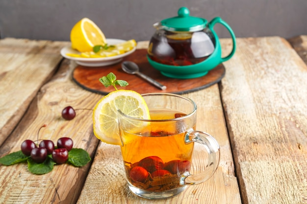 Black tea in a glass cup with mint cherries and lemon on a wooden table next to fresh cherries and a teapot on a stand and lemon in a plate