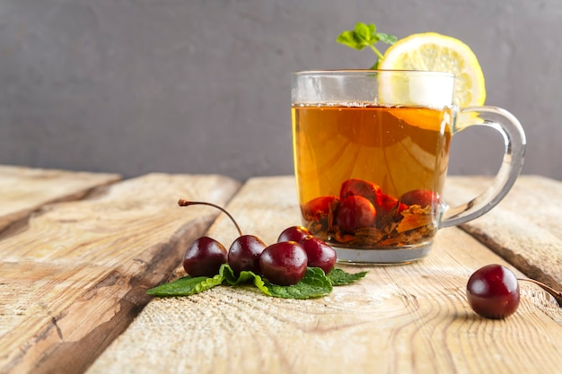 Black tea in a glass cup with mint cherries and lemon on a wooden table near fresh cherries. horizontal photo