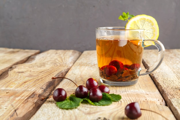Black tea in a glass cup with mint cherries and lemon on a wooden table near fresh cherries