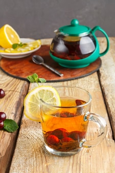 Black tea in a glass cup with mint cherries and lemon on a wooden table and a teapot and lemon in a plate and mint leaves.