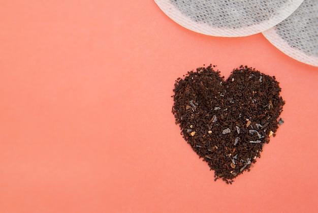 Black tea heart shape isolated on pink . tea isolated.