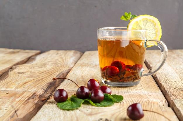 신선한 체리 근처 나무 테이블에 민트 체리와 레몬 유리 컵에 홍차