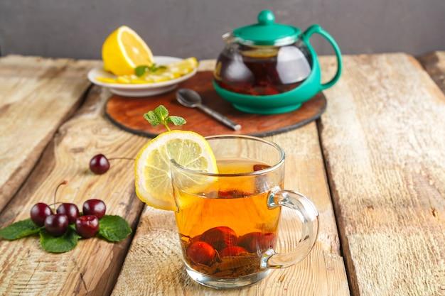 신선한 체리 옆에 나무 테이블에 민트 체리와 레몬 유리 컵에 홍차와 스탠드에 주전자와 접시에 레몬