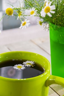 Chamomiles와 함께 녹색 컵에 홍차.