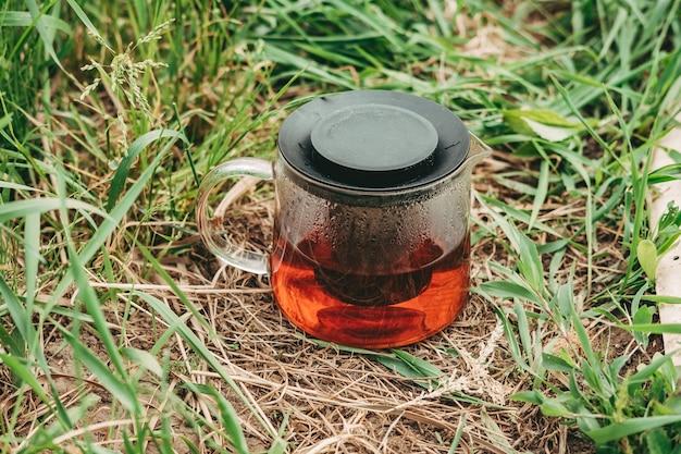Черный чай в прозрачном чайнике на зеленой траве. полезный горячий чай на природе. чайник крупным планом. конденсат на стекле чайника. освежающий чай.
