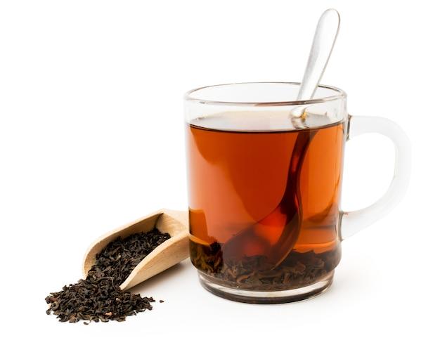 Черный чай в стеклянной изолированной чашке и деревянной ложке на белизне.