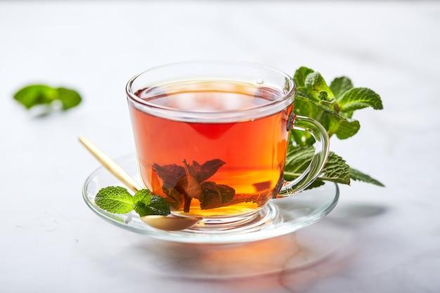 紅茶のストレスを和らげるミントの葉が入ったガラスの透明マグカップに入った紅茶