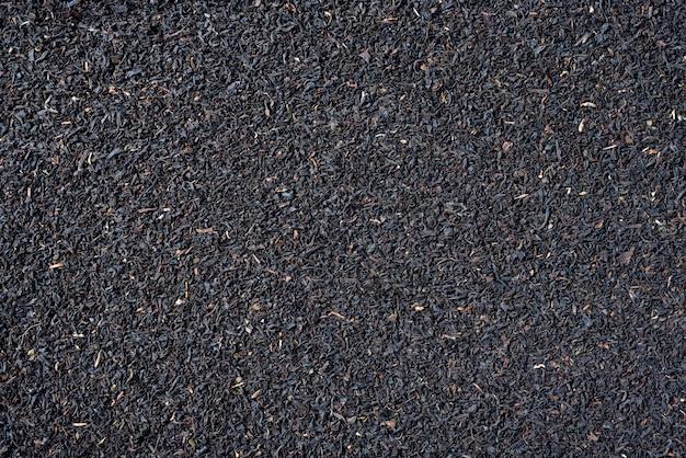 Black tea loose dried tea leaves, marco. food background.