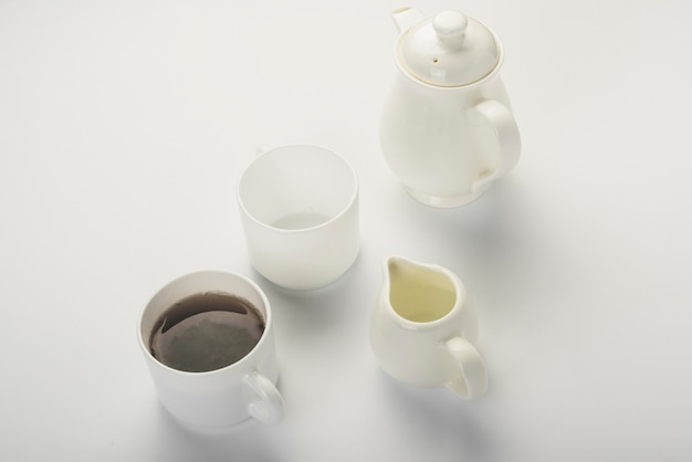 Black tea; milk jug; white cup and teapot isolated on white backdrop