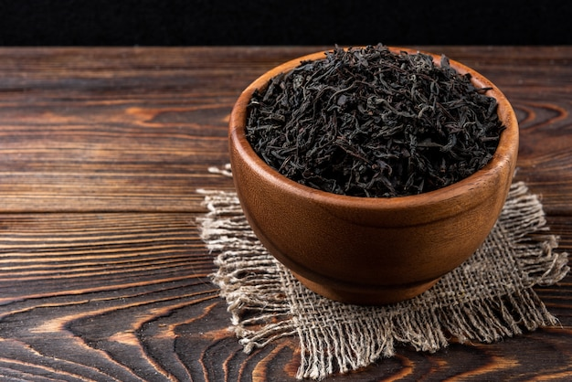 Черный чай на темном деревянном фоне.