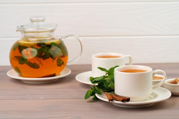 茶色のテーブルにシナモンスティックとミントを添えた紅茶