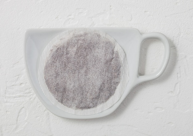 明るい背景にカップの形をしたセラミックプレート上の紅茶ティーバッグ。