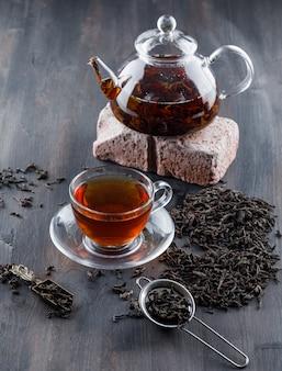 Tè nero in teiera e tazza con tè asciutto, vista dell'angolo alto del mattone su una superficie di legno