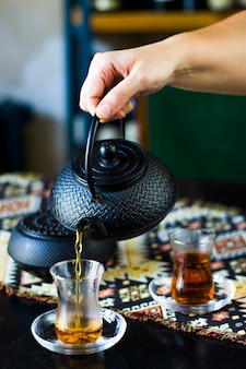 Black tea and teapot in hand, turkish tea glasses and old iron teapot