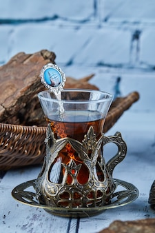Black tea in a traditional glass cup and cookies on blue wooden table