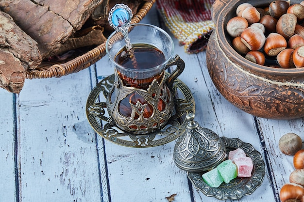 Black tea in a traditional glass cup with candies and a bowl of hazelnuts on blue wooden table