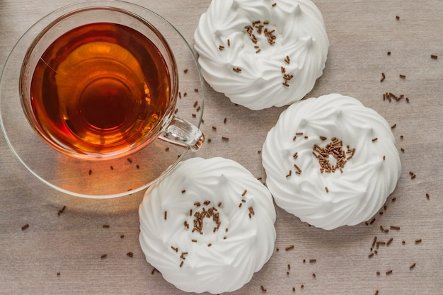 Black tea in transparent cup an air homemade meringues close up