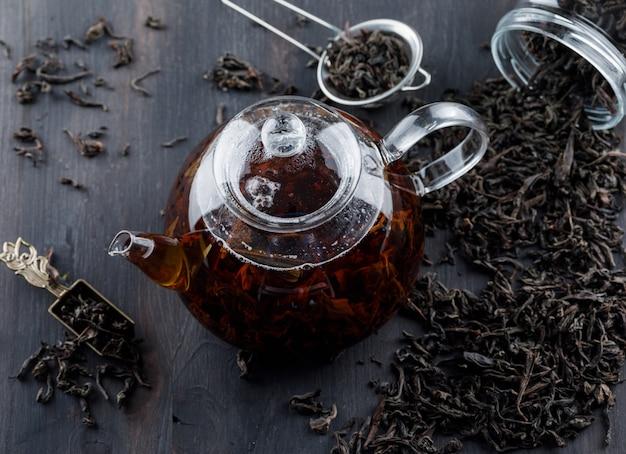 Черный чай с сухим чаем в чайнике на деревянной поверхности