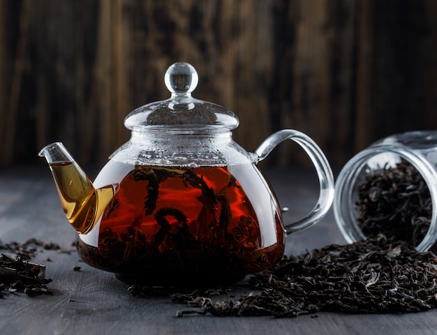 Tè nero con tè asciutto in una teiera su superficie di legno, vista laterale
