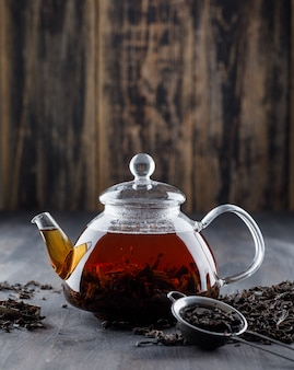 Black tea with dry tea in a teapot on wooden surface