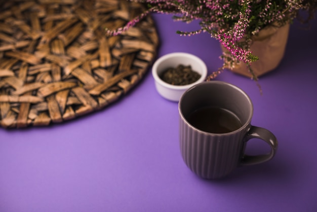 Black tea with herbs and coaster on purple background