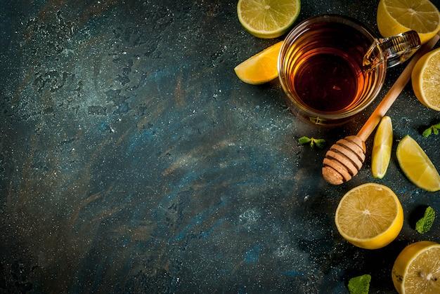 Black tea with lemon and mint on dark blue concrete stone scene top view