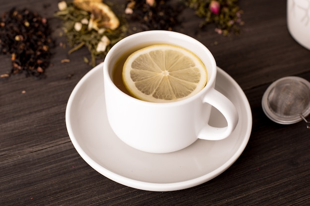 Black tea with lemon and several views of tea on a wooden table