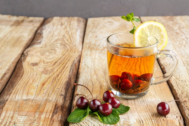 Black tea with mint cherries and lemon on a wooden table next to fresh cherries. horizontal photo
