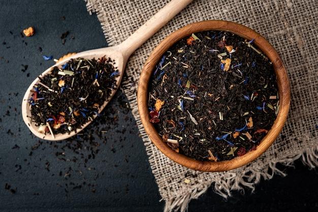 黒の背景に木製のボウルにローズヒップとリンゴと紅茶。