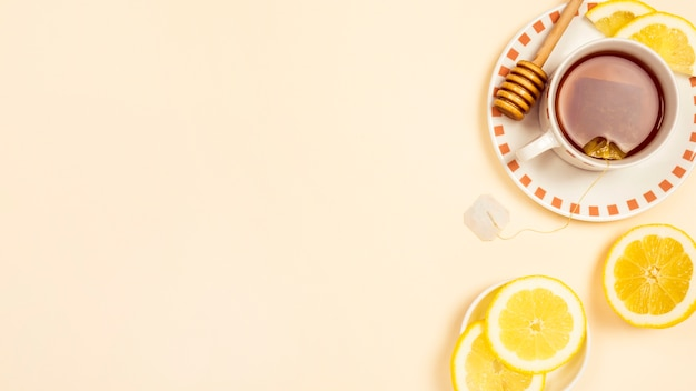 Black tea with slice of fresh lemon on beige background