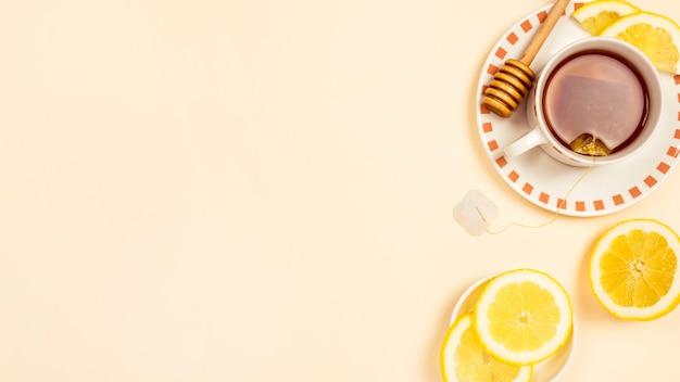 ベージュ色の背景に新鮮なレモンのスライスと紅茶