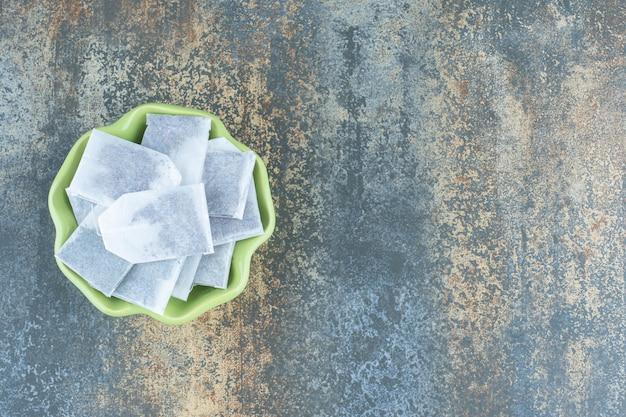 Bustine di tè nere in ciotola verde su fondo di marmo.