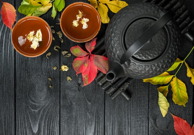 Black teapot and green tea with jasmine in a clay cup, on a black and wooden  with autumn leaves food  top view