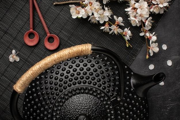 Черный чайник с веткой сакуры и палочками для еды на темноте