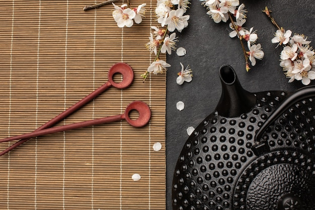 Black teapot with sakura branch and chopsticks on a dark background.