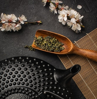 Black teapot with sakura branch and green tea on a dark background.