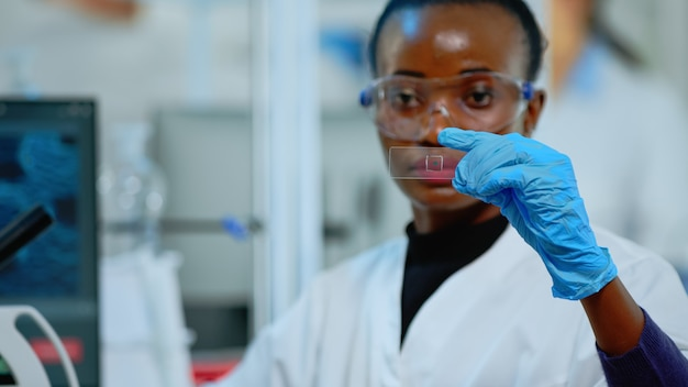Black technician doing experiment in modern equipped lab looking at result. african scientist working with various bacteria tissue and blood samples, concept of pharmaceutical research for antibiotics