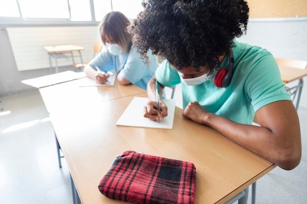 Black teen boy wearing face mask in class high school student writing copy space education