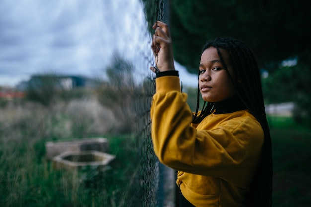 Black teenage girl, holding on to a fence, with dramatic and sad expression