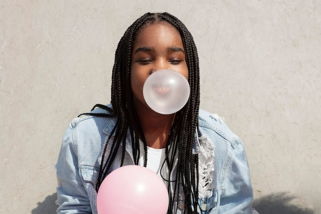ガムの泡を作って遊んでいる黒人の10代の少女