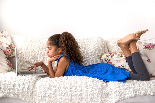 Черная девочка-подросток сидит на диване с ноутбуком
