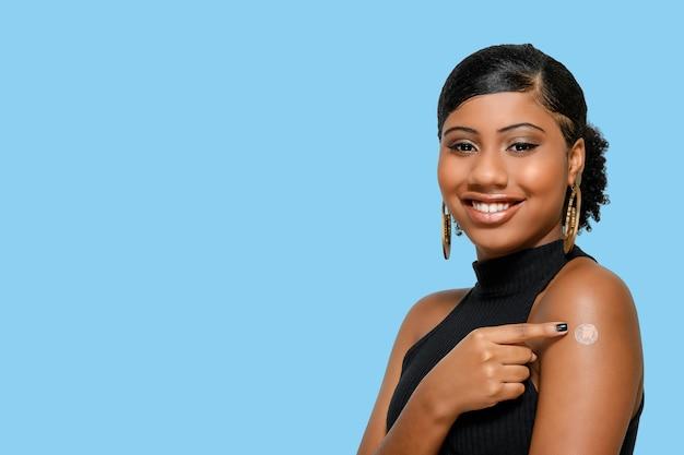 幸せに笑って、青で隔離された彼女の腕にワクチンマークを示す黒の10代の少女