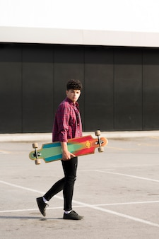 Black teenager in plaid shirt walking with longboard