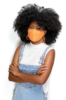 白い背景で隔離のcovid19に対して顔の保護マスクを身に着けている黒のティーンエイジャー