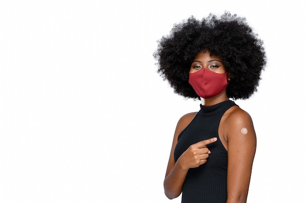 Covid19に対する保護マスクを身に着けている黒いティーンエイジャーはワクチンブランドを示しています