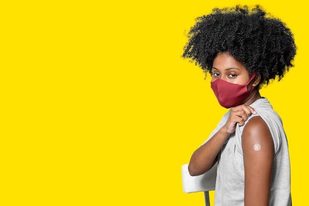 Черный подросток в защитной маске от covid19 с улыбкой на лице показывает вакцину b