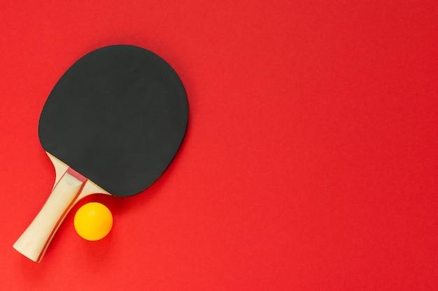 빨간색 표면에 고립 된 검은 테니스 탁구 라켓, 탁구 스포츠 장비