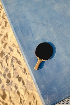 Black tennis racquet on a blue table outside at the beach sand on a sunny day