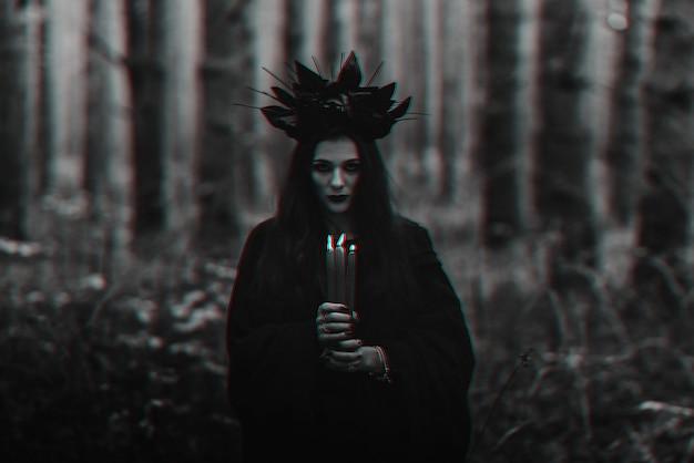 Black terrible witch holds candles in her hands. black and white with 3d glitch virtual reality effect