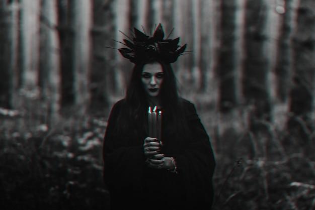 검은 끔찍한 마녀가 양초를 손에 들고 있습니다. 3d 글리치 가상 현실 효과가 있는 흑백 프리미엄 사진